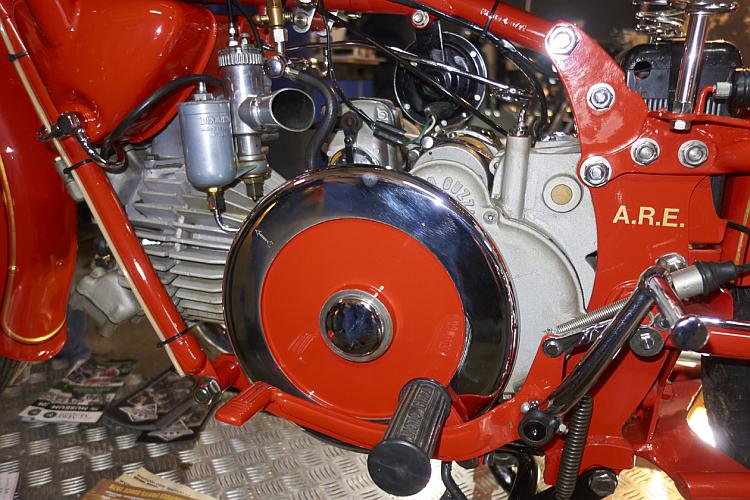 A classic or vinage motorcycle engine with a bright red frame and flywheel