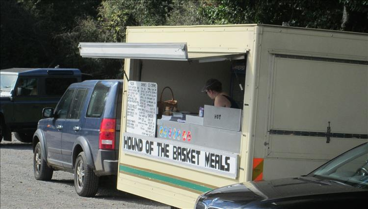 A food van with a sign on the front stating hound of the basket meals at hound tor