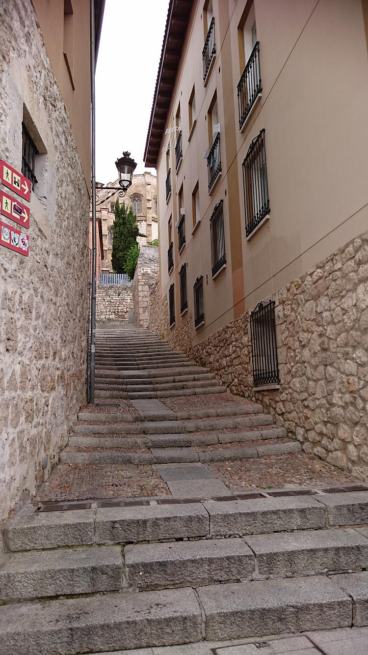 An old and worn stairway makes it's way up a narrow gap between buidlings in Burgos