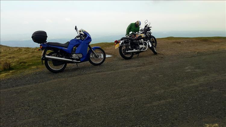 2 motorcycles atop of the hill, but all we can really see is mist in the distance