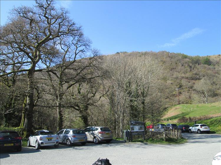A gravel car park among leafless trees and green hills near Aber Falls