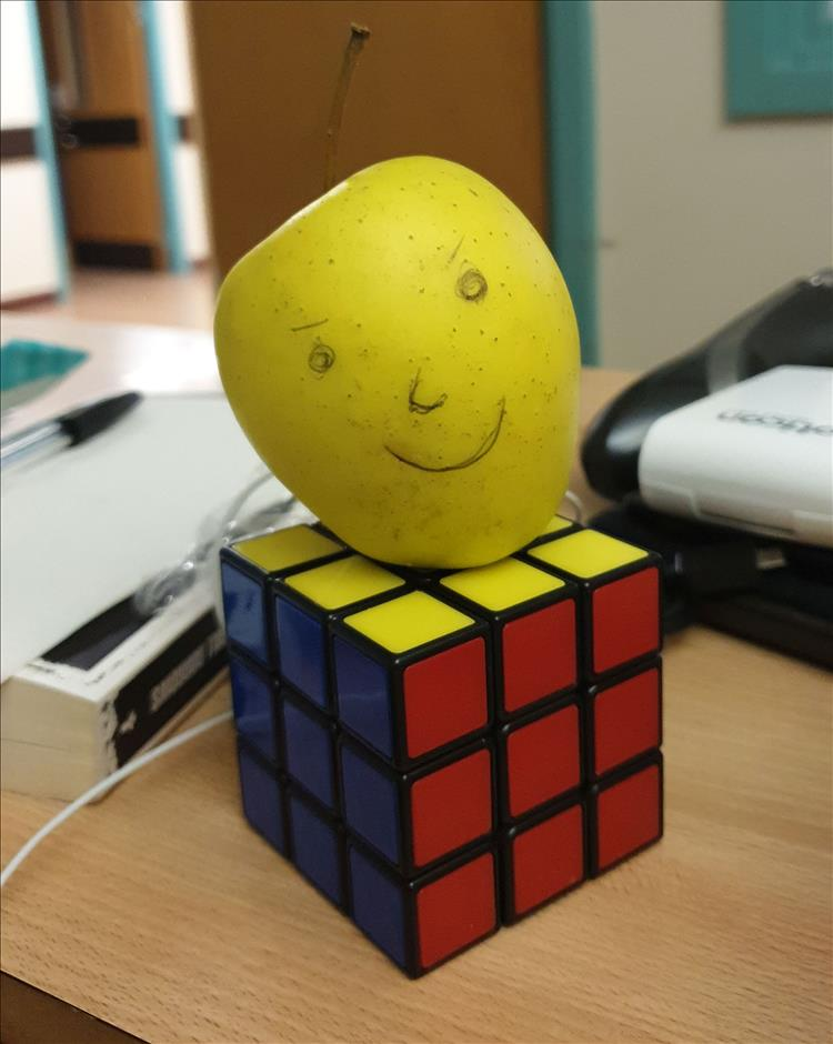 An apple with a face drawn on it placed on a rubik's cube