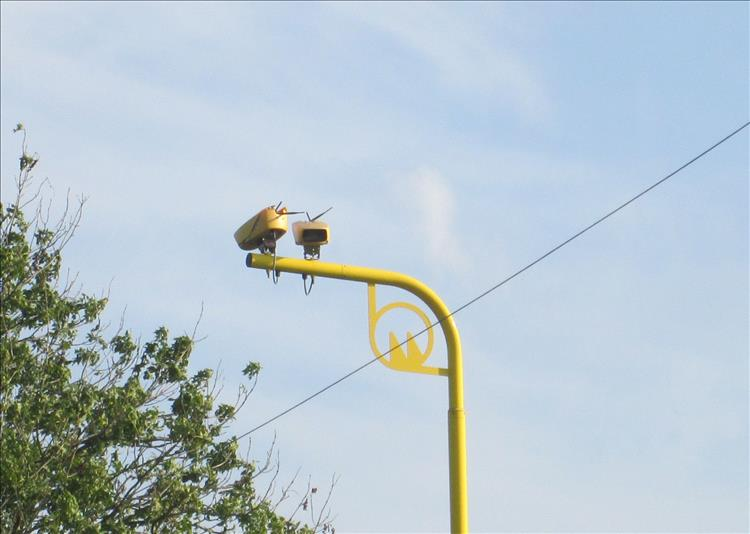 2 cameras in yellow housings point up and down the road on top of a bright yellow pole