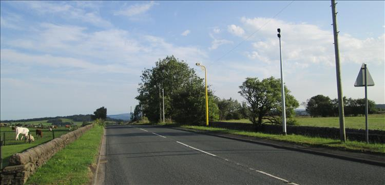 A regular countryside road with an average speed camera to one side