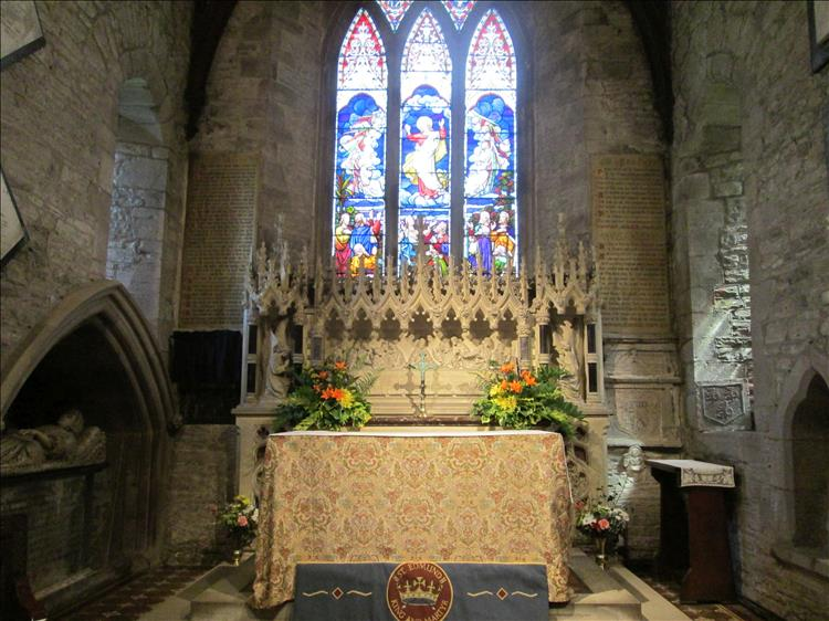 Inside the church alter has ornate carved stonework and detailed bright stained glass windows