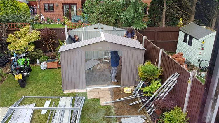 Looking down from a window we see several people holding on to the shed as it's being put up