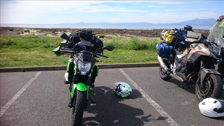 Sharon's 250 with wobbly luggage, calm waters firth of clyde and arran in the hazy distance