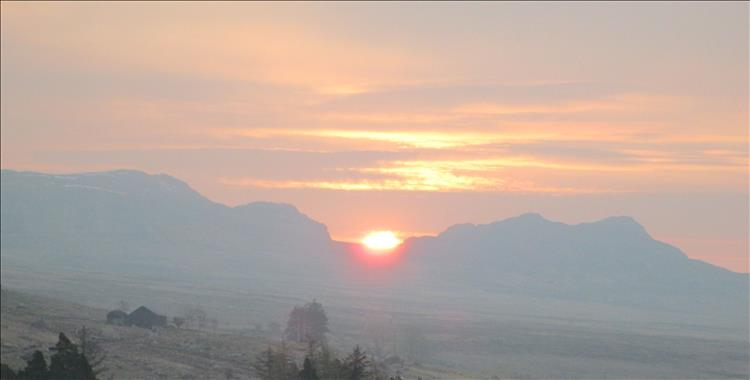 The orange sun rises between two mountain peaks in North Wales Snowdonia
