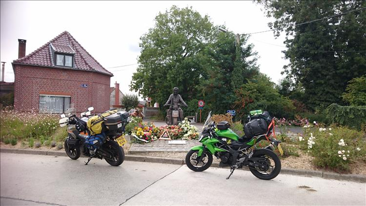 A statue featuring a world war 2 motorcyclist surrounded by flowers and the small village