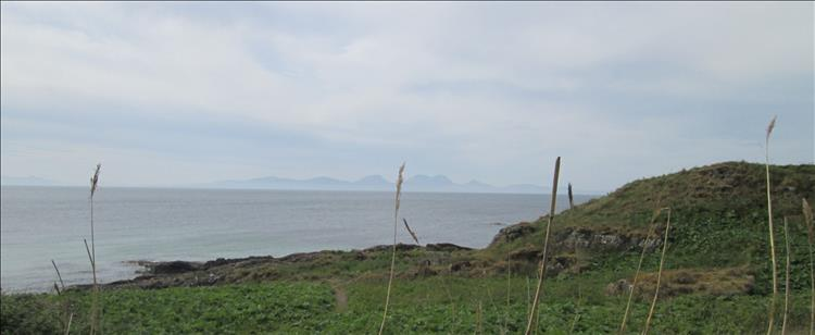 Across hazy waters in the distance the isle of Islay has steep hills pointing up