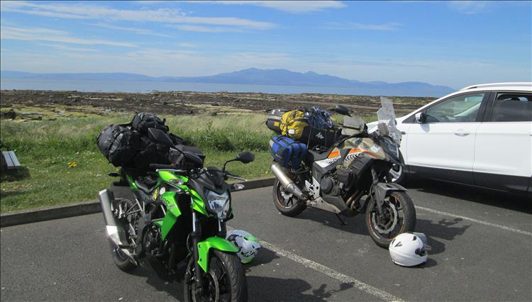 2 motorcycles overladen with camping kit and the Isle of Arron in the misty distance
