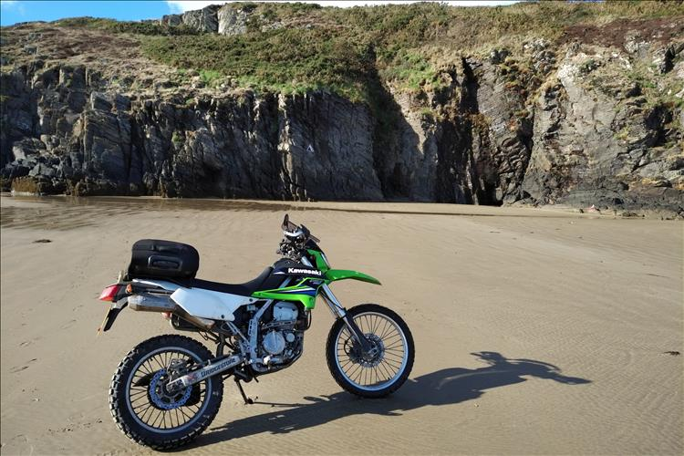 Bob's KLX250 motorcycle set in a beach with steep rocky cliffs