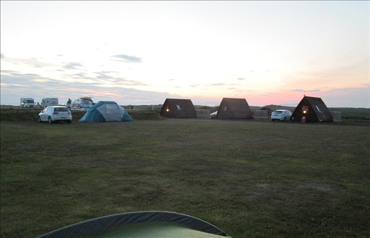 The light is fading over tents, pods, campervans and caravans at the site