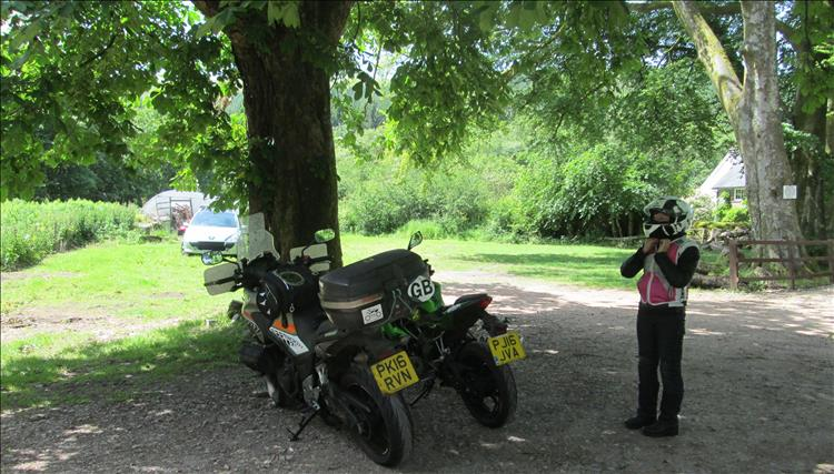 2 motorcycles among trees and sunshine near the cafe in the Beacons