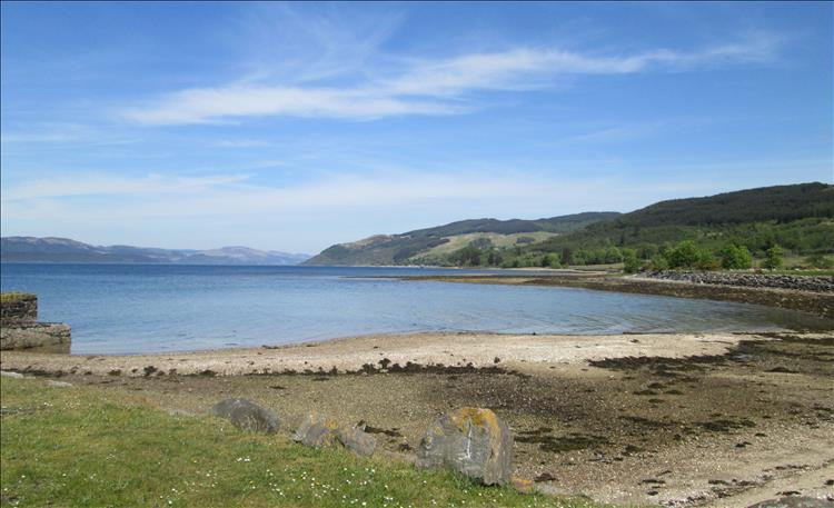 A sandy and stony beach, a very calm Loch Fyne and endless hills in the distance