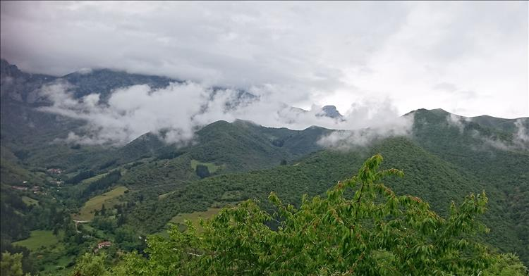 Lush green mountains amidst mist and clouds in Northern Spain