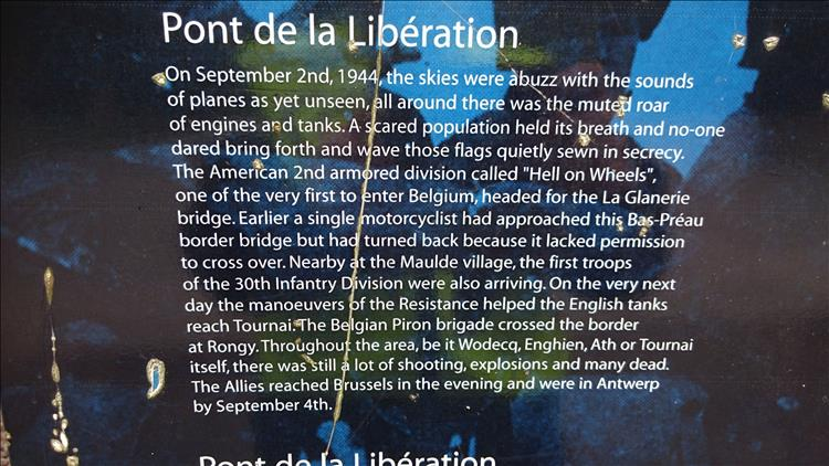 A sign in English telling the tale of an American WW2 motorcyclist accidentally came in to liberate belgium