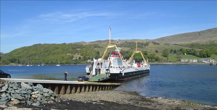 The ferry from Bute to the mainland on the northern tip. Blue skies, tree covered hills and the calm loch