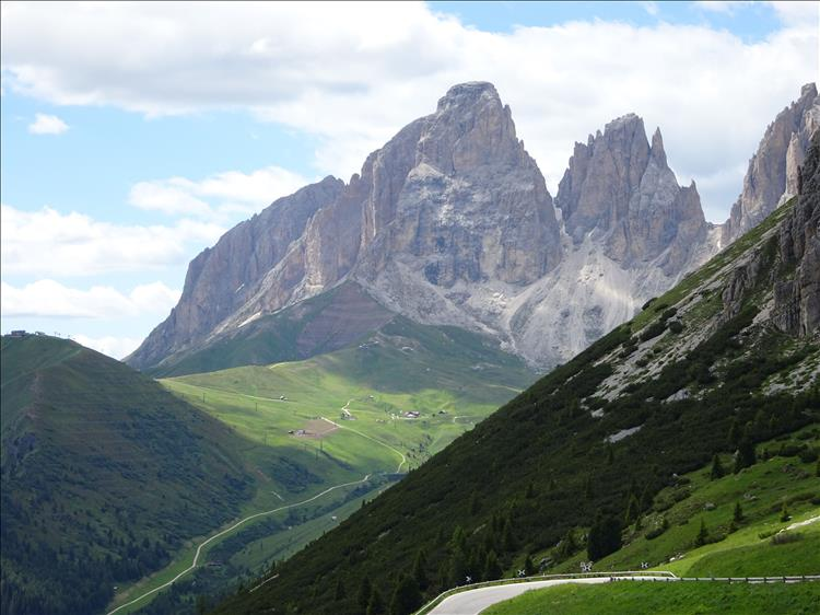 A road winds between steep green hillside and enormous rocky mountain tops in the Dolomites