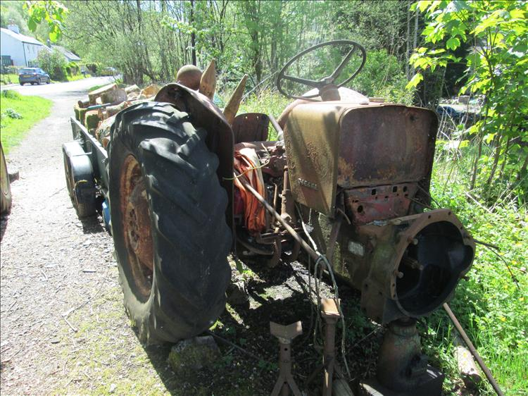 The rusting remains of a tractor, missing everything forward of the steering wheel