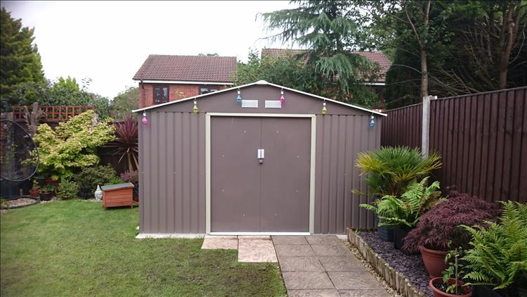 The new shed seen from the front. Made of metal and looks huge compared to the old shed