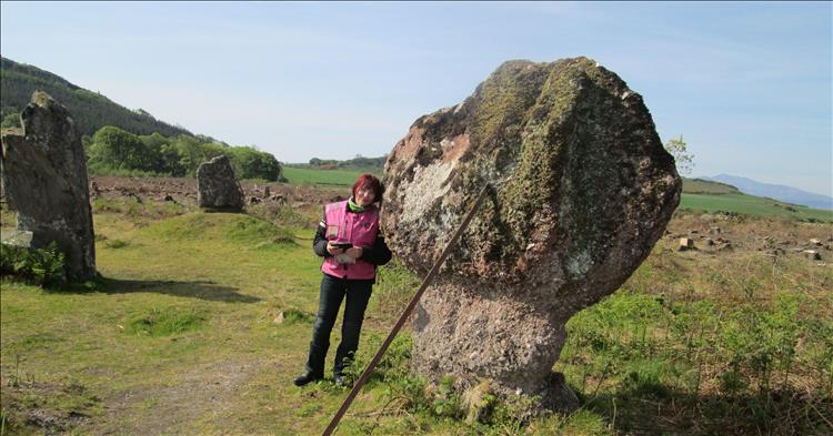 Sharon leans against one of the 3 standing stones on open ground with tree stumps all around