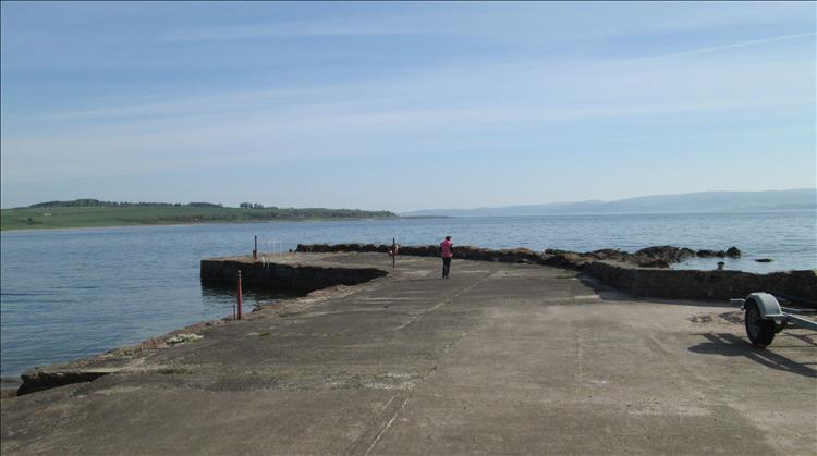 Sharon stands on a small harbour wall overlooking a very calm Clyde estuary