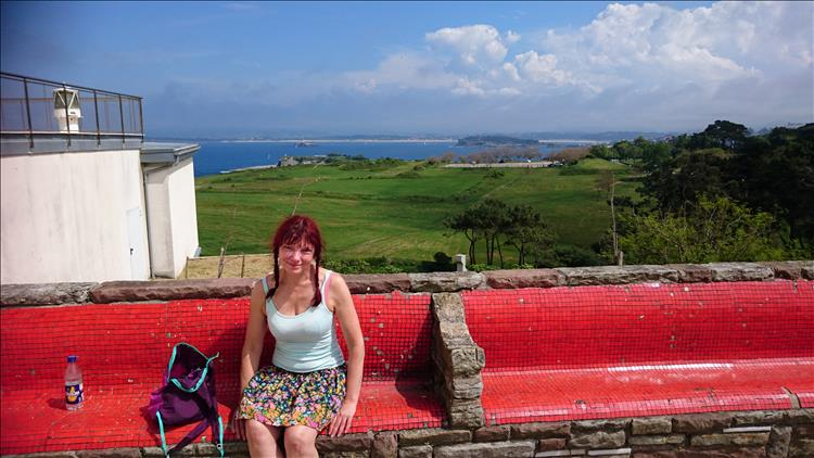 Sharon in vest top and skirt sitting beside the large white lighthouse at Cabo Mayor