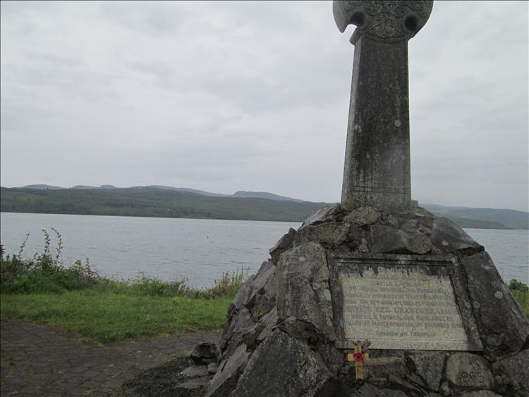 A stone cross and plaque with misty moist hills across the calm flat Holy Loch