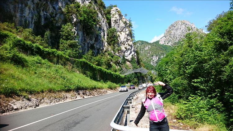 A deep gorge with steep white stone side, the road runs through it and Sharon is happy in th sun