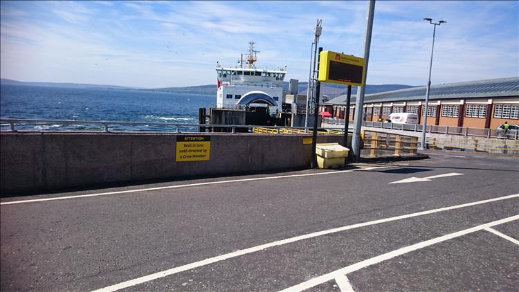 The ferry is in dock and the front bow doors are open as traffic rolls off