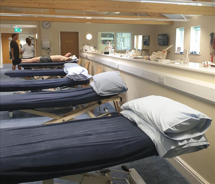 A row of beds in the crisp smart building with a patient and nurse in shot