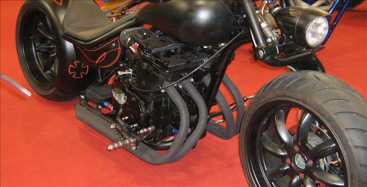 A custom motorcycle at a show with exhaust pipes with no silencers at all