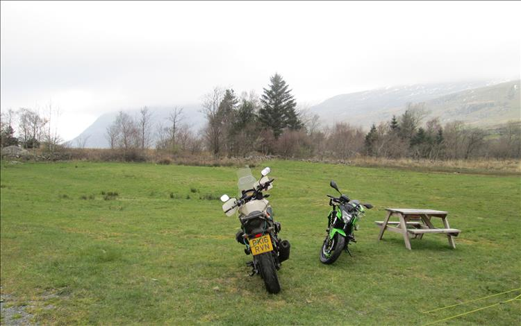 The 2 motorbikes set against misty grey skies in the morning at the campsite