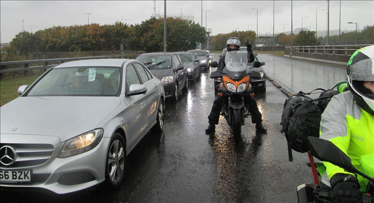 A rider on his Suzuki give a big thumbs up in the pouring rain while queuing for the Erutunnel