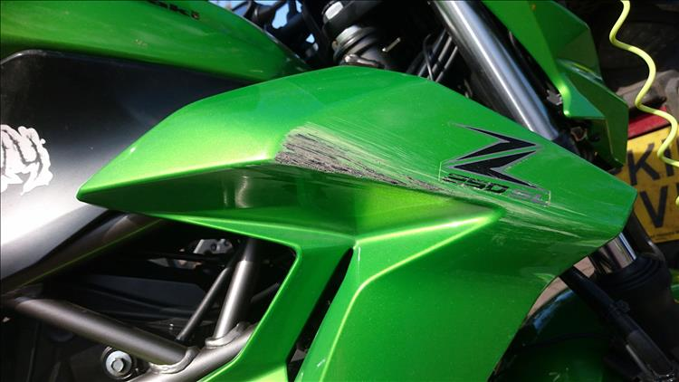 The bright green side panel has deep scratches through the paint to the black plastic below