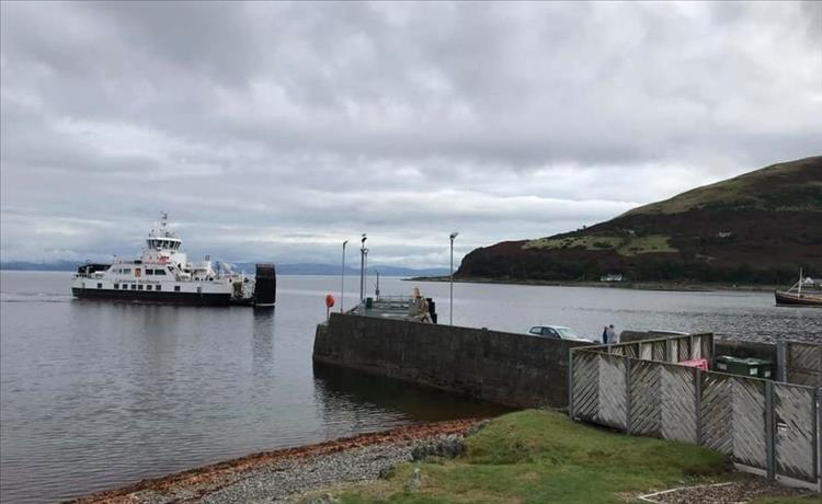 A small car ferry in the small port at Lochranza under grey skies but calm waters