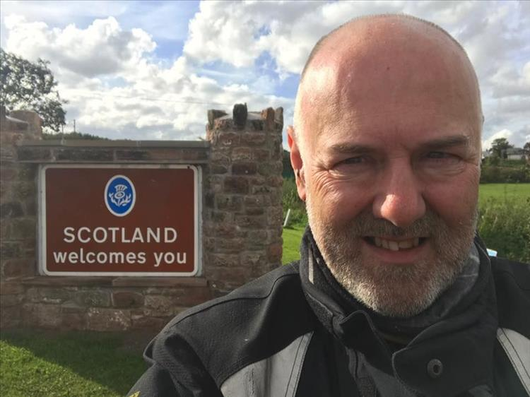 "Andy smiles standing in front of a brown ""Scotland welcomes you"" sign at Gretna Green"