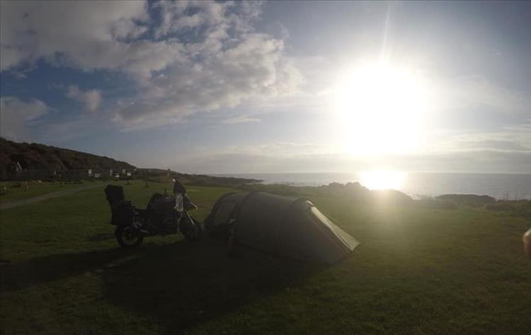 The tent and the bike at the campsite. Beautiful scenery, bright sun in light cloud and the sea