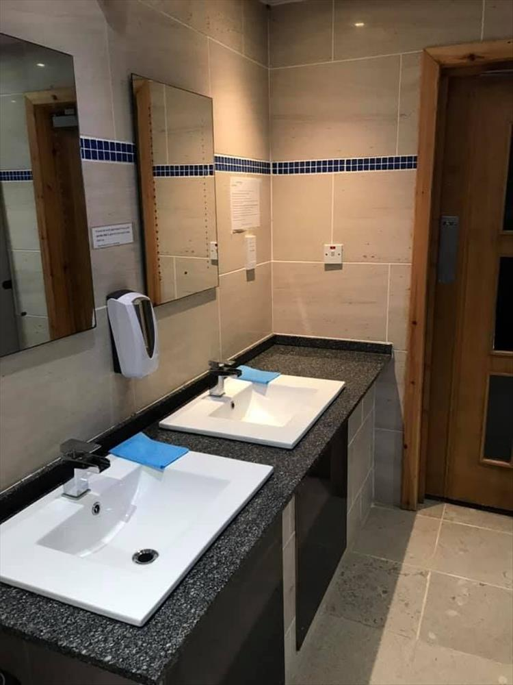 Smart sinks, mirrors and taps in clean tiled room at Port Ban