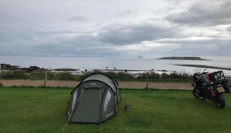 Andy's tent and motorcycle looking out over the waters on a grey yet beautiful scene