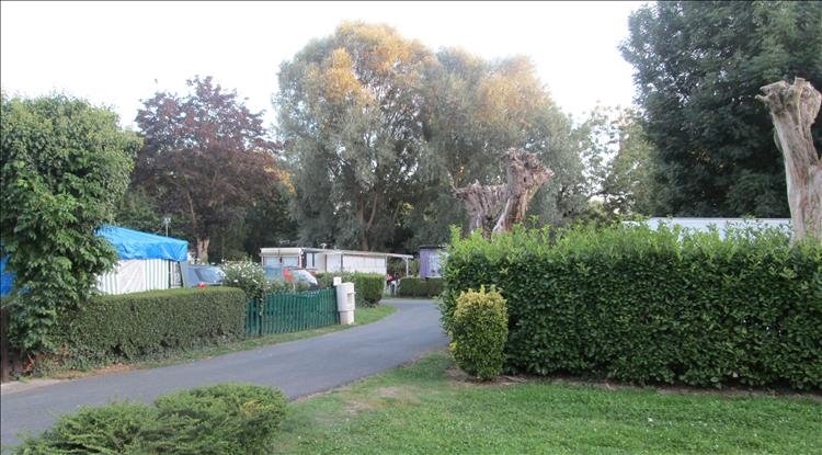 Trees, caravans, sheds and grass at the campsite in Arleux