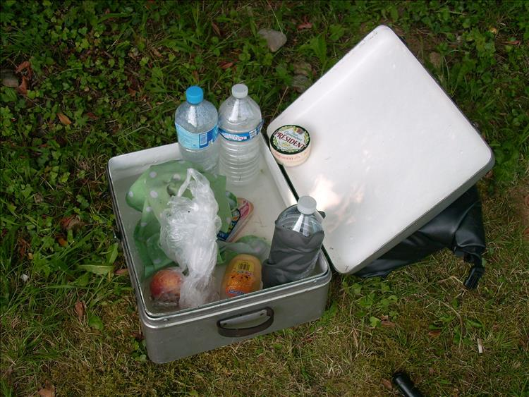 An aluminium motorcycle pannier filled with water and food for cooling