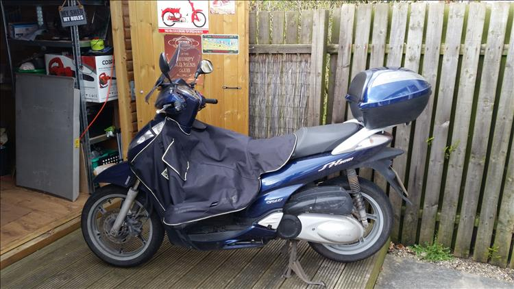 Boogers sh300 honda scooter outside his shed with a material leg cover fitted