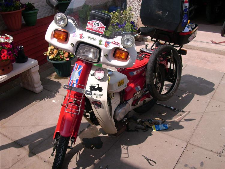A C90 with a few bits of kit and even a spare tyre in a small garden while Bogger fixes it