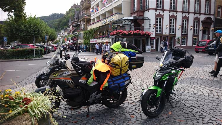 CB500X and Z250SL camping luggage on the main street of Cochem with all the tourists