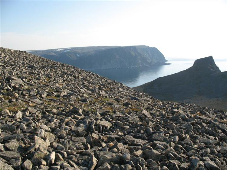 Steep rubble strewn hillsides lead down to the rocky outcrops and the sea at Cape Nordkinn