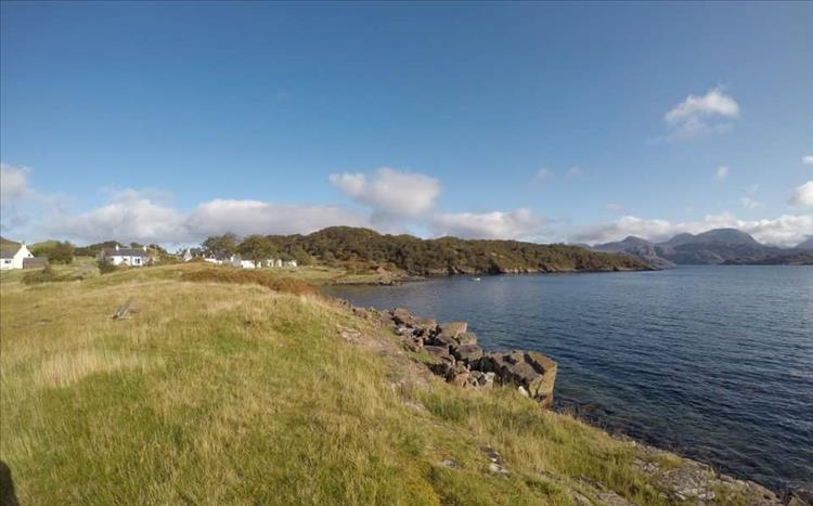 The calm sea and sunshine next to small white highland houses and thick lush grasses