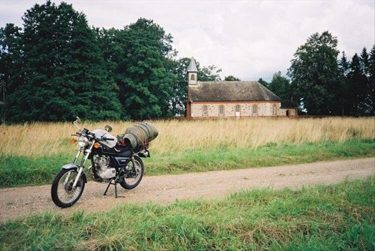 The 125 on a compacted dirt track with trees and a chapel in the background