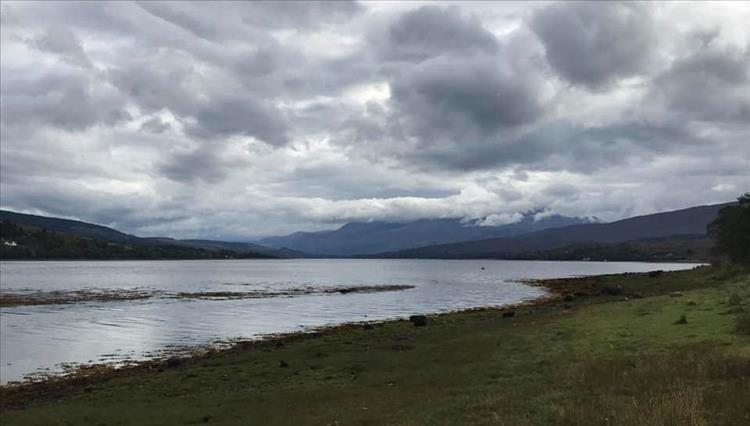 Thick heavy clouds, grassy shoreline and mountains in the mist all at Loch Eil near Fort William